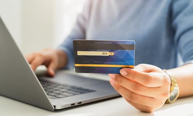 Frauenhand, die eine kreditkarte hält und einen laptop für online-einkauf auf einem weißen schreibtisch verwendet.
