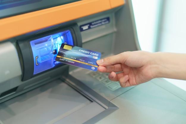 Frauenhand, die eine kreditkarte in bankautomaten einführt, um geld am geldautomaten abzuheben.
