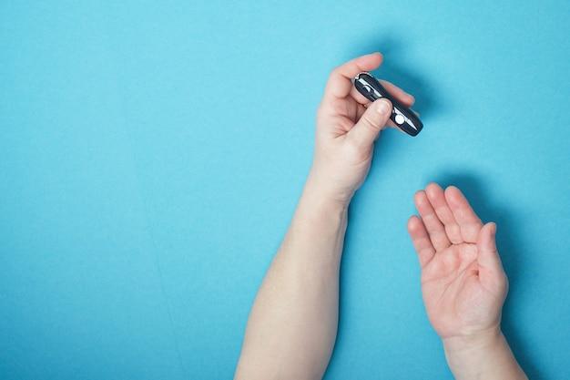 Frauenhand, die eine lanzette an ihrem finger verwendet, um blutzucker unter verwendung eines glukosemessgeräts ,, diabetes, glykämie, gesundheitskonzept zu überprüfen. draufsicht des blauen hintergrundkopierraums