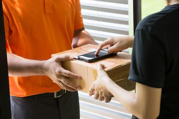 Frauenhand, die eine lieferung von kästen vom lieferboteen annimmt und am handy unterzeichnet