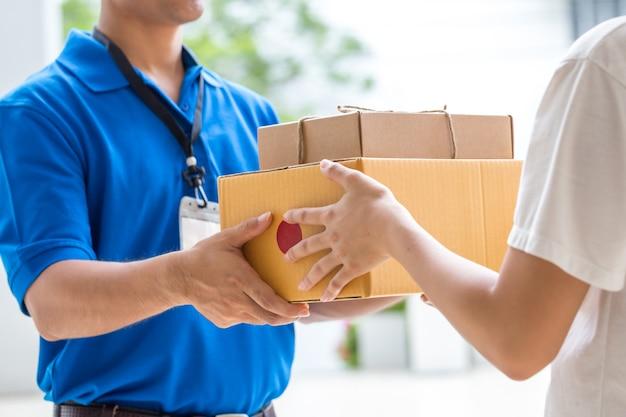 Frauenhand, die eine lieferung von kästen vom lieferboteen annimmt