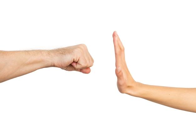 Frauenhand, die eine mannfaust auf einem weißen hintergrund stoppt. gewalt gegen frauen