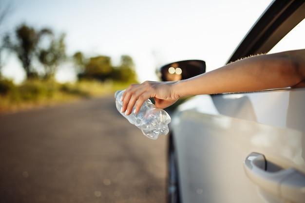 Frauenhand, die eine plastikflasche aus dem autofenster wirft.