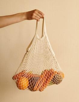 Frauenhand, die eine schnureinkaufstasche mit gemüse, früchte in den warmen erdigen tönen hält