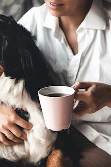 Frauenhand, die eine tasse kaffee und einen berner sennenhund hält, schnüffelt, was in der tasse ist