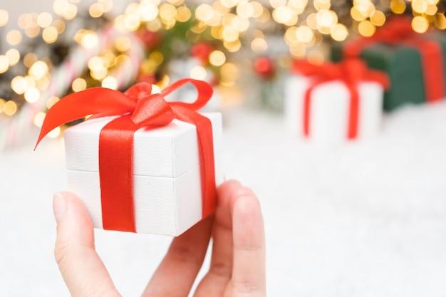 Frauenhand, die eine weiße geschenkbox mit einem roten band hält