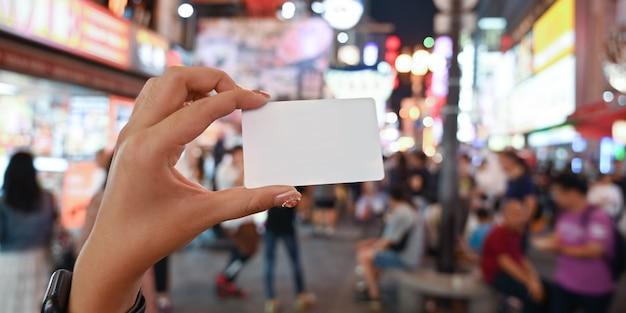 Frauenhand, die eine weiße leere karte über überfüllten leuten am nachtstraßenmarkt als hintergrund hält. weiße leere karte für anzeigenkonzept.
