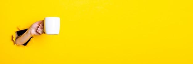 Frauenhand, die eine weiße tasse auf einem hellen gelben hintergrund hält
