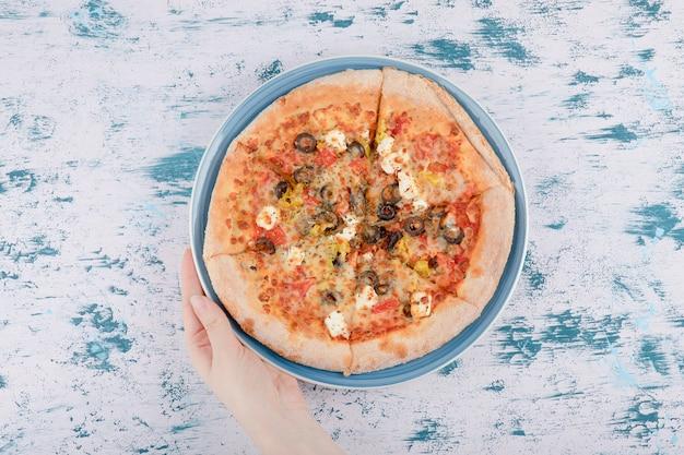 Frauenhand, die einen blauen teller mit heißer pizza auf einem marmorhintergrund d hält.