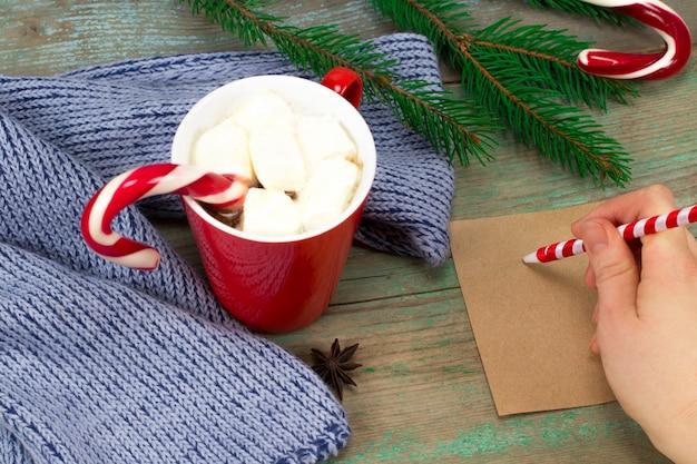 Frauenhand, die einen brief auf einem hölzernen hintergrund mit weihnachtsschmuck schreibt.