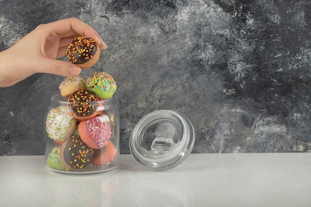 Frauenhand, die einen donut aus einem glas nimmt.