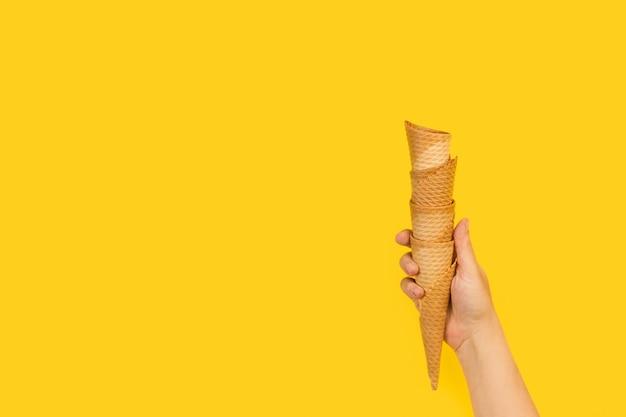 Frauenhand, die einen haufen waffelkegel auf einem gelben hintergrund mit kopienraum hält