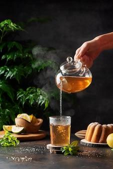 Frauenhand, die einen heißen schwarzen tee gießt