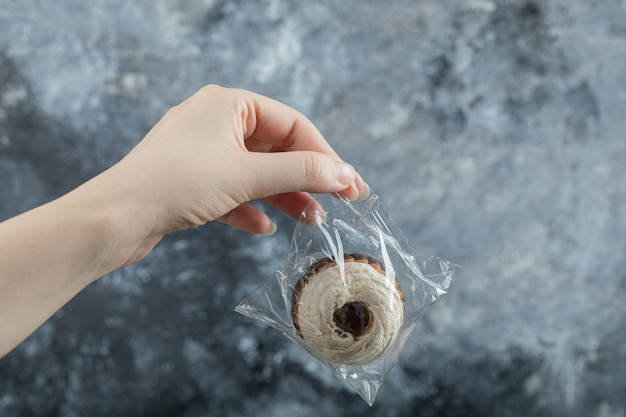 Frauenhand, die einen köstlichen kleinen kuchen hält
