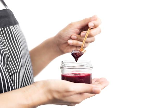Frauenhand, die einen löffel mit beerenmarmelade im glas hält