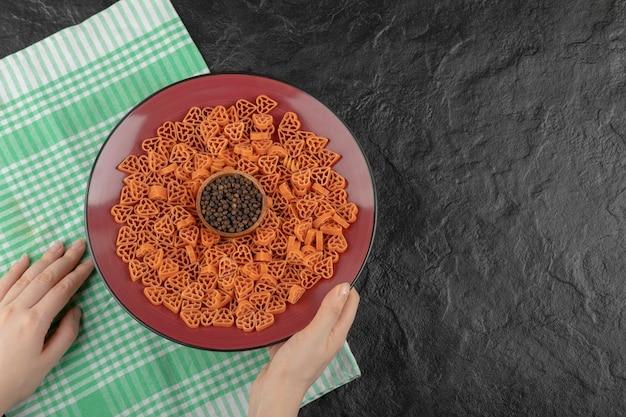 Frauenhand, die einen teller mit roher pasta in herzform auf schwarzem tisch hält