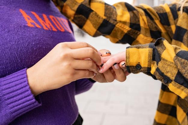 Frauenhand, die einer anderen frau einen ring legt