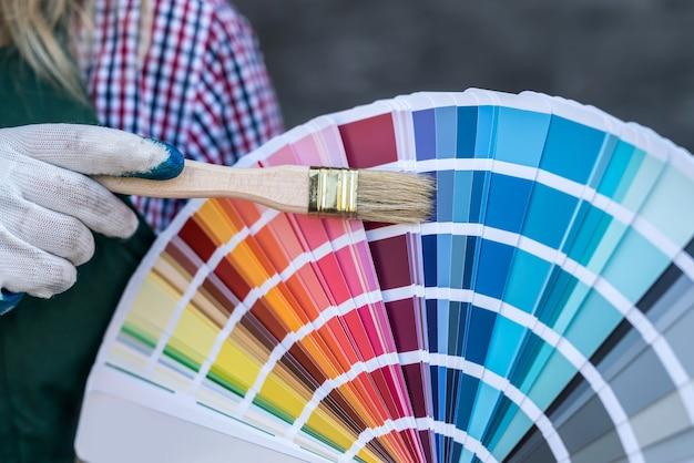 Frauenhand, die farbpalette für reparatur hält