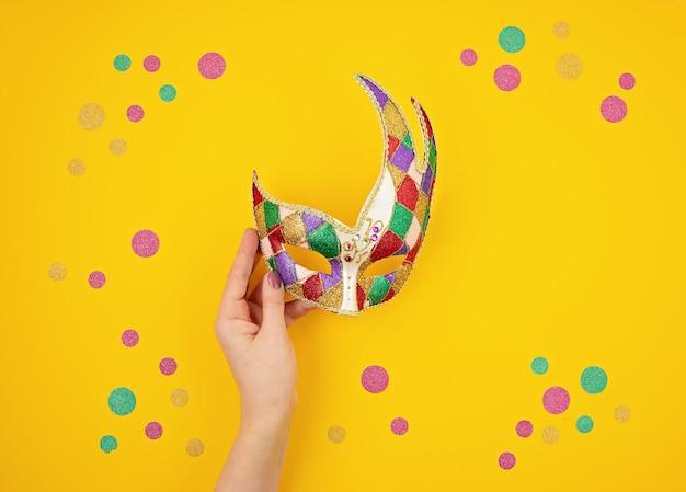 Frauenhand, die festliche, bunte karneval- oder karnevalsmaske über gelber wand hält. flache lage, draufsicht