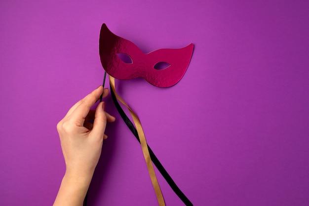 Frauenhand, die festliche, bunte karneval- oder karnevalsmaske über lila wand hält. flache lage, draufsicht