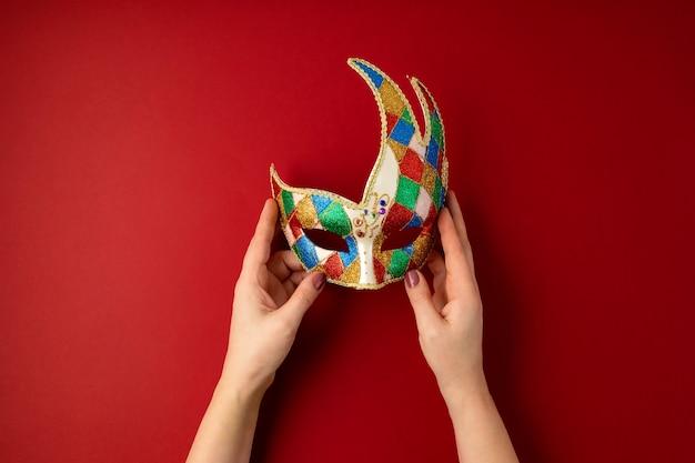 Frauenhand, die festliche, bunte karneval- oder karnevalsmaske über roter wand hält. flache lage, draufsicht
