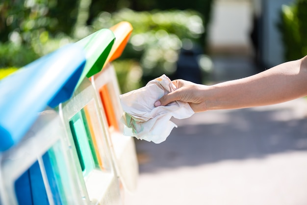 Frauenhand, die fragepapierabfall in abfallabfall hält und setzt.