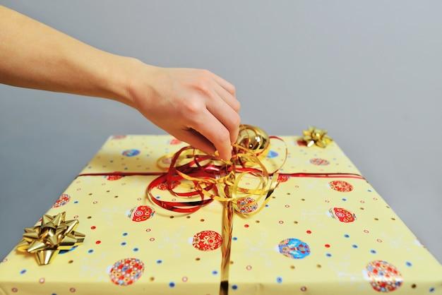 Frauenhand, die gelbe geschenkbox öffnet. frauenhände, die geschenkbox öffnen