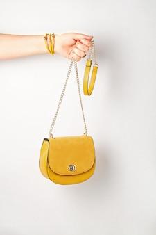 Frauenhand, die gelbe weibliche handtasche hält.
