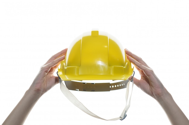 Frauenhand, die gelben sicherheitshelm lokalisiert hält.