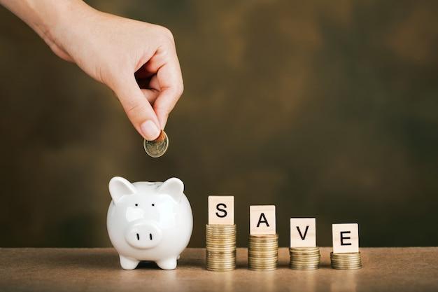 Frauenhand, die geldmünze in sparschwein für das sparen von geld setzt. geld sparen und finanzielles konzept