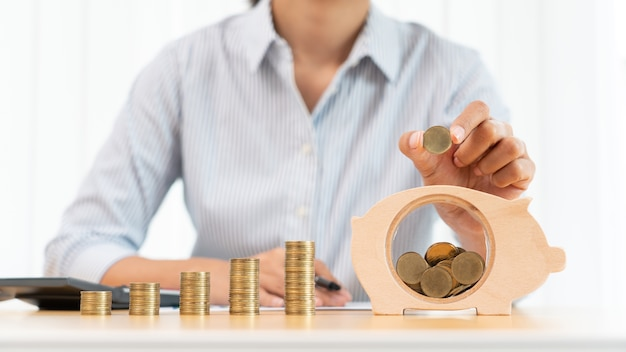 Frauenhand, die geldmünze in sparschwein mit schritt des wachsens von stapelmünzen für das sparen von geld für zukünftiges investitionskonzept setzt.
