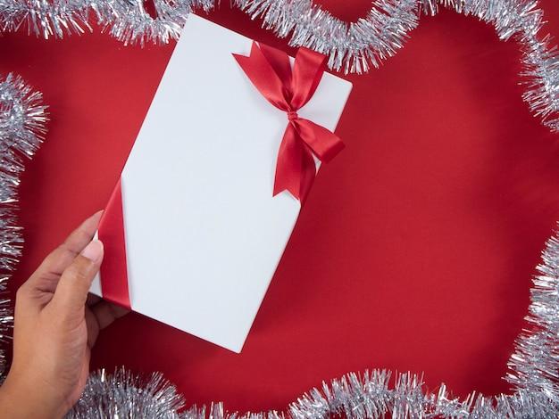 Frauenhand, die geschenkbox gebunden mit rotem band hält