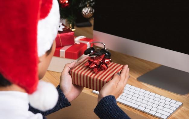 Frauenhand, die geschenkbox im weihnachtsfeiertag im büro mit weihnachtsdekoration hält
