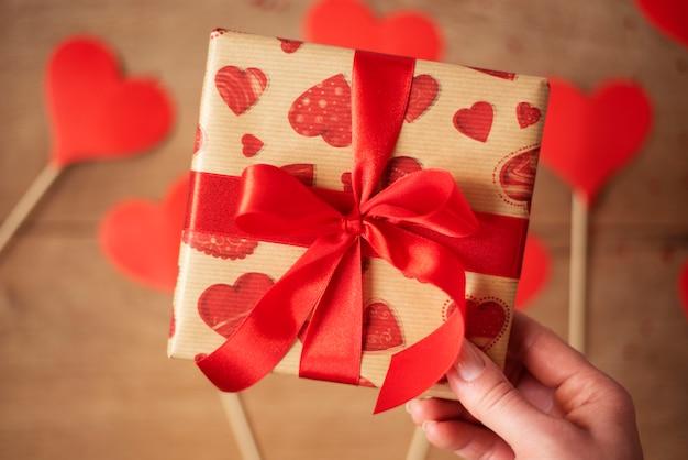 Frauenhand, die geschenkbox mit roter schleife hält. viele herzen auf einem holz in defokus. valentinstag konzept