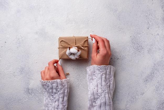 Frauenhand, die geschenkkästen im kraftpapier einwickelt.