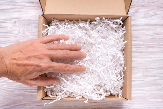 Frauenhand, die geschredderten papierfüller zum pappkarton setzt