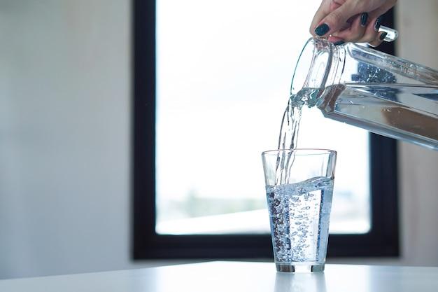 Frauenhand, die glas wasser hält und wasser in ein glas gießt
