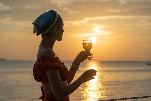 Frauenhand, die glas wein gegen einen schönen sonnenuntergang nahe meer am tropischen strand, nah oben hält