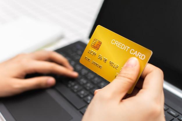 Frauenhand, die goldene kreditkarte hält und laptop-computer verwendet online-shopping-konzept