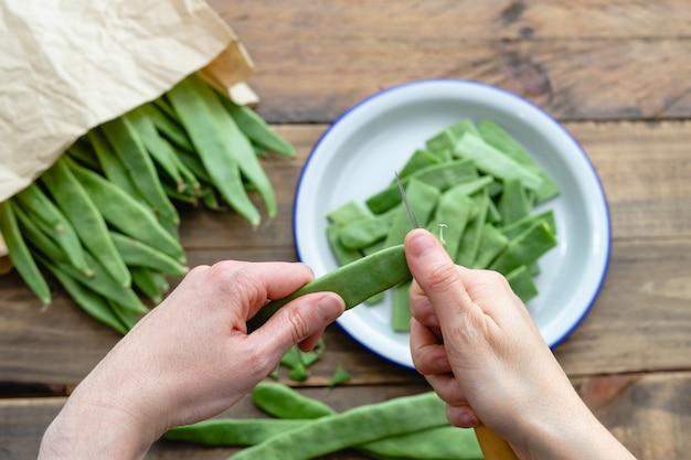 Frauenhand, die grüne bohnen zum kochen schneidet. konzept der lebensmittelzubereitung. ansicht von oben