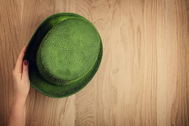 Frauenhand, die grünen zylinder hält. symbol der heiligen patrick feier.