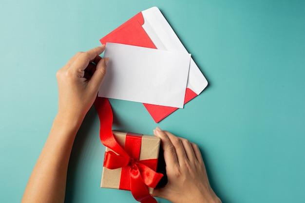 Frauenhand, die grußkarte und geschenkbox hält