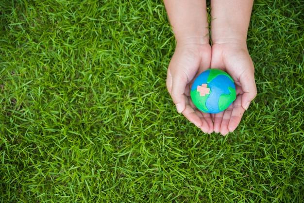 Frauenhand, die handgemachte kugel auf feldhintergrund des grünen grases hält.