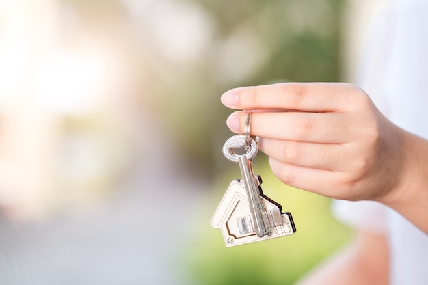 Frauenhand, die hauptschlüssel hält. konzept für das immobiliengeschäft.