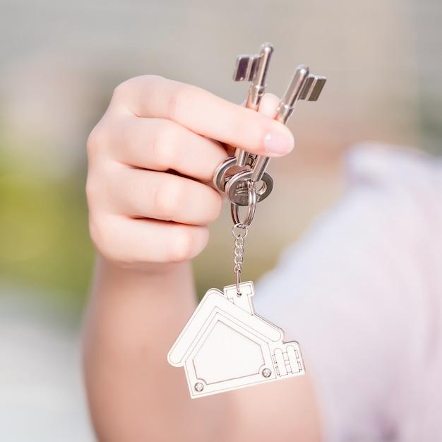 Frauenhand, die hauptschlüsselkonzept für immobiliengeschäft hält