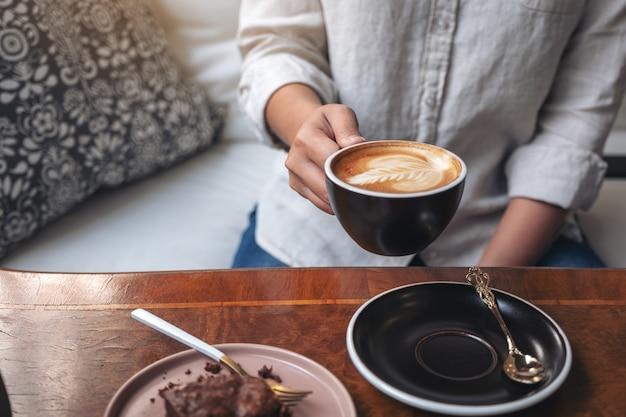 Frauenhand, die heißen lattekaffee mit brownie-kuchen auf dem tisch hält und trinkt