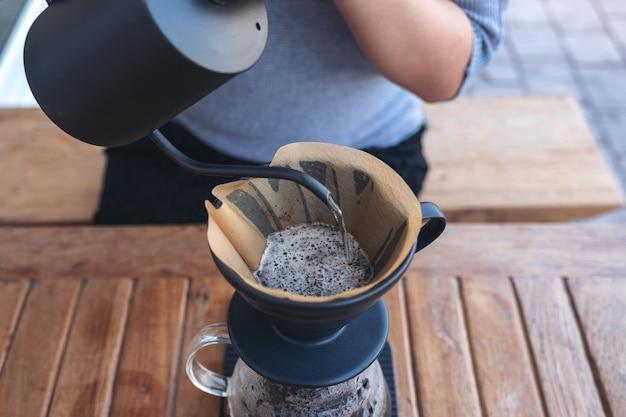 Frauenhand, die heißes wasser gießt, um einen tropfkaffee auf vintage holztisch zu machen