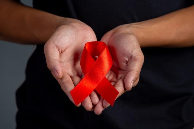 Frauenhand, die hiv-bewusstseinskonzept des roten bandes welt-aids-tag und welttag der sexuellen gesundheit hält.