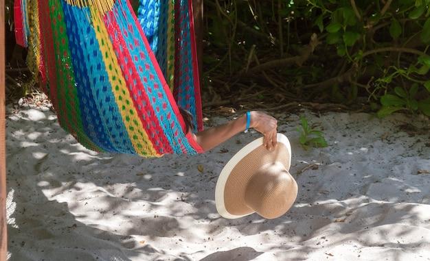Frauenhand, die hut von einer hängematte nahe dem strand hält