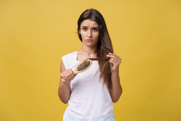 Frauenhand, die ihr langes haar mit blick auf beschädigte, spaltende enden von haarpflegeproblemen hält.